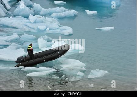 a man on rubber boat on Jokulsarlon Glacier Lake, Iceland - Stock Photo