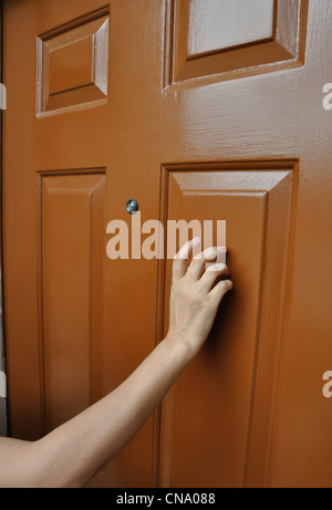 Hand tapping on the door - Stock Photo