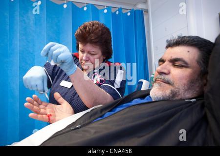 A nurse stitches a mans hand in A&E - Stock Photo