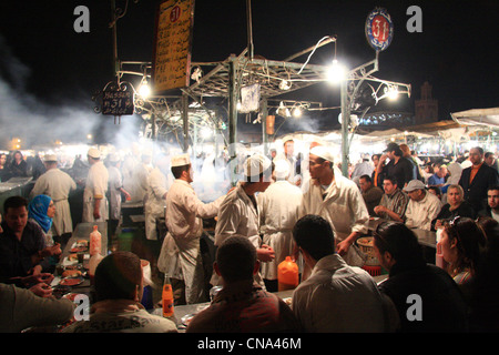 Tourists and Moroccans eat at a busy food grill in the heart of Place Djemaa el-fna in Marrakech,Morocco, North - Stock Photo