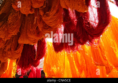 Freshly dyed red and orange skeins of wool hang drying in the sunlight at the Wool Dyers souk in the medina, Marrakech,Morocco - Stock Photo