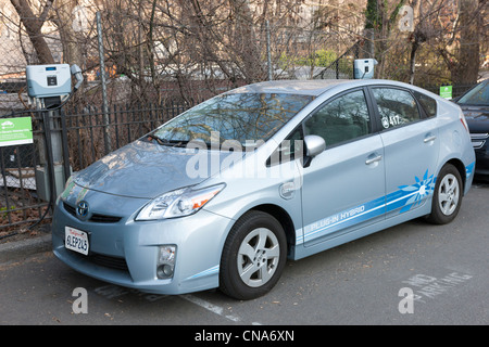 A Toyota Prius hybrid electric car, used by the New York City Parks department, receives a charge at a charging - Stock Photo