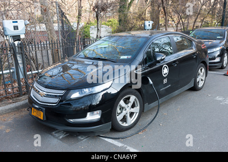 A Chevy Volt hybrid electric car, used by the New York City Parks department, receives a charge at a charging station - Stock Photo