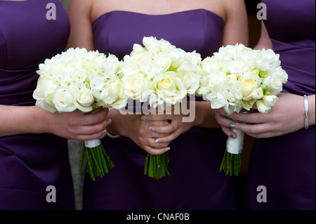 three bridesmaids holding wedding bouquets of roses - Stock Photo