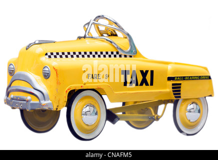 Kid's size small version of a vintage Yellow New York Taxi Cab. A push bike pedal car. Cut out isolated on a white - Stock Photo
