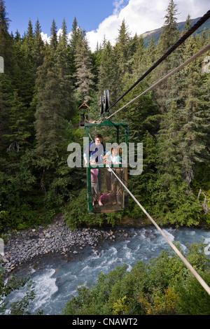 Two women and their daughters ride the hand tram across Winner Creek near Girdwood, Southcentral Alaska, Summer - Stock Photo
