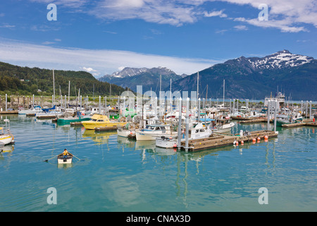 Children rowing a small dingy in tthe Haines Small Boat Harbor next to Commercial fishing boats, Alaska - Stock Photo