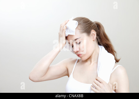 Woman dabbing sweat with towel - Stock Photo