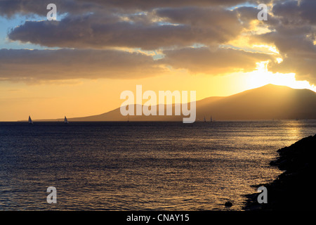 Sun setting over mountains and water - Stock Photo