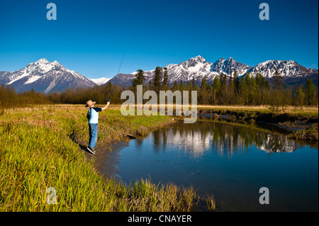 A young boy fishing on Rabbit Slough on a sunny spring day in the Matanuska-Susitna Valley, Southcentral Alaska - Stock Photo