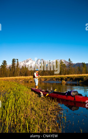 Man with a kayak fishing from the shore of Rabbit Slough in the Palmer Haystack Flats wildlife refuge, Mat-Su Valley, - Stock Photo