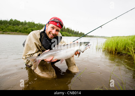 Fly fisherman holds up a Sockeye salmon on the Mulchatna River in the Bristol Bay area, Southwest Alaska, Summer - Stock Photo