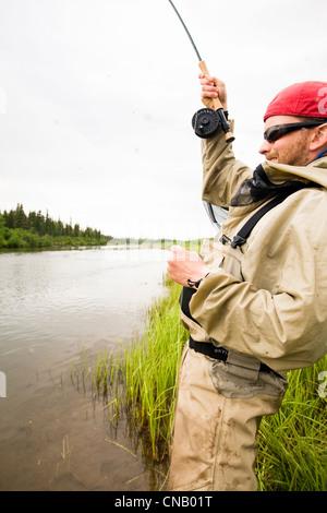 Fly fisherman fishing for salmon on the Mulchatna River in the Bristol Bay area, Southwest Alaska, Summer - Stock Photo