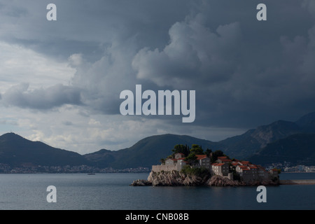 Houses on island in still lake - Stock Photo