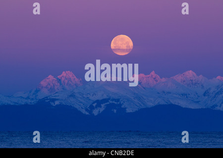 Full moon setting behind the Chilkat Mountains and Lynn Canal at sunrise, Inside Passage, Southeast Alaska, Winter - Stock Photo