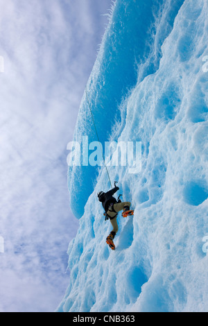 An ice climber ascends the face of a large iceberg frozen into Mendenhall Lake, Juneau, Southeast Alaska, Winter - Stock Photo