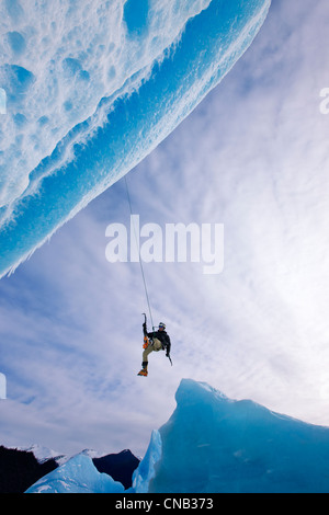 An ice climber swings down from rope to reach face of a large iceberg frozen into Mendenhall Lake, Juneau, Alaska, - Stock Photo