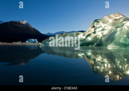 An iceberg, trapped in the frozen waters of Mendenhall Lake glowing and backlit with the morning sun, Juneau, Alaska, - Stock Photo