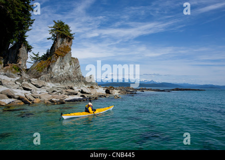 A water level view of a sea kayaker paddling in calm waters along a shoreline near Juneau, Inside Passage, Alaska - Stock Photo