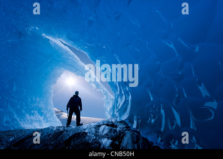 COMPOSITE: View from inside an ice cave of an iceberg frozen in Mendenhall Lake as an ice climber stands at the - Stock Photo