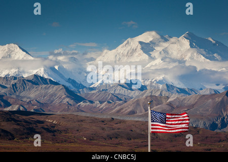 An American flag flys in the wind at Eielson Visitor Center with Mt. Mckinley in the background,  Denali National - Stock Photo
