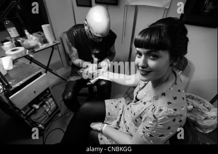 Tattooists from around the world work at The Edinburgh Tattoo Convention 2012 in Edinburgh, Scotland. - Stock Photo