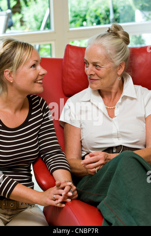 Eldery lady listening to her daughter - Stock Photo