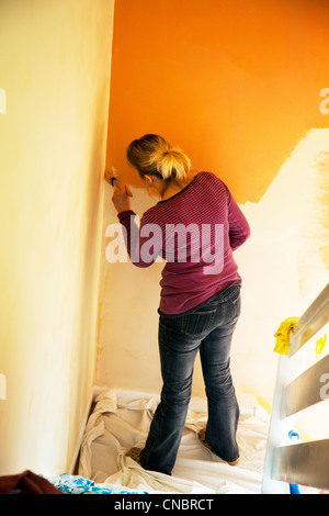 Lady, woman decorating hall and stairway painting walls with brush ...