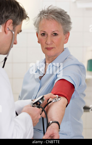 Doctor checking blood pressure - Stock Photo