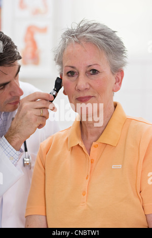 Doctor examining ears of a female patient - Stock Photo