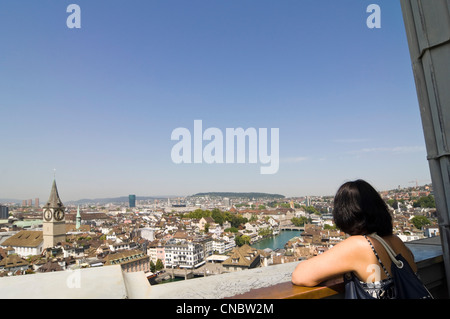 Horizontal wide angle of a woman enjoying the view of historical centre of Zürich on a bright sunny day from the - Stock Photo