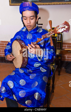 Vertical close up view of traditional Vietnamese musician playing the dan nguyet or Full Moon lute guitar in costume. - Stock Photo