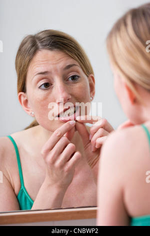 Woman looking at her underlip - Stock Photo