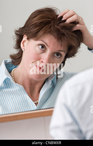 Midage woman looking at her hair - Stock Photo