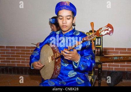 Horizontal close up view of traditional Vietnamese musician playing the dan nguyet or Full Moon lute guitar in costume. - Stock Photo