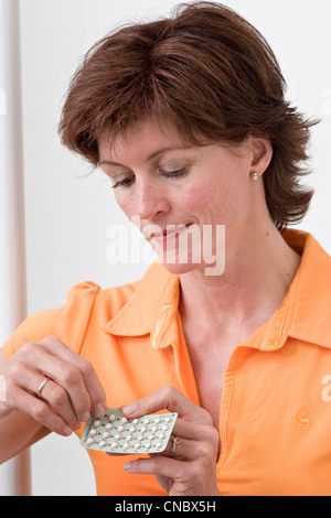 Middle aged woman taking pills - Stock Photo
