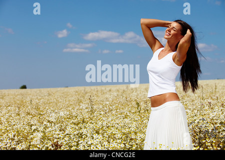 Young woman dressed in white standing among chamomiles on a sunny day - Stock Photo