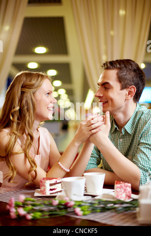 A young happy woman and her boyfriend having nice time in restaurant - Stock Photo