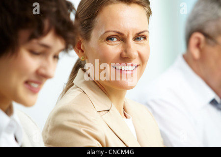 Smiling business woman looking at camera among her partners - Stock Photo