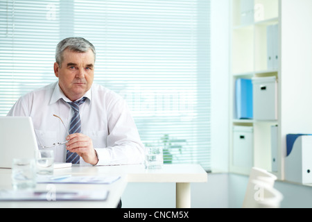 Mature businessman at his workplace in office - Stock Photo