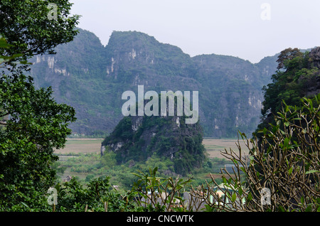 Landscape from Bich Dong pagoda towards Bich dong village. Trees in foreground and karst mountain in the middle. - Stock Photo