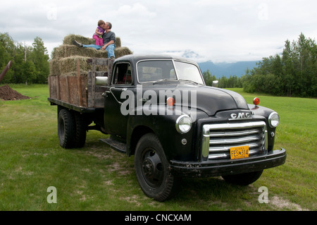 Grandfather kisses his granddaughter as they sit on hay bales stacked on the back of a classic truck, Palmer, Alaska - Stock Photo