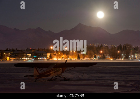 A full moon rises over the Chugach Mountains with a ski plane parked on the frozen Lake Hood in the foreground, - Stock Photo