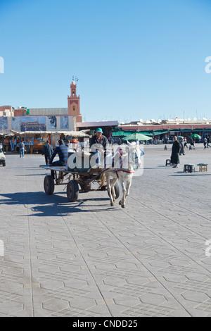 donkey cart crossing the square Jemaa el Fna (Marrakesh) - Stock Photo