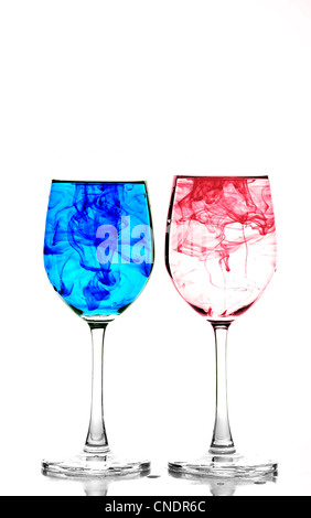 Two wine glasses filled with water and spreading red and blue ink - Stock Photo