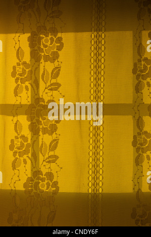 Backlit lace curtain illuminated by the setting sun - Stock Photo