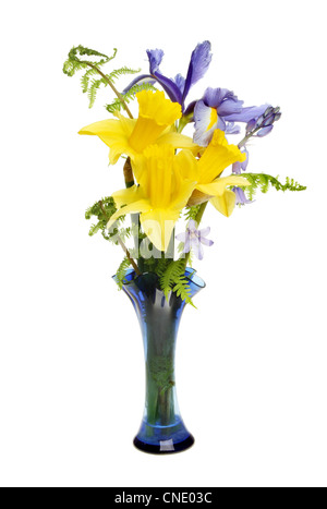 Arrangement of daffodil, iris and bluebell flowers with fern fronds in a glass vase isolated against white - Stock Photo