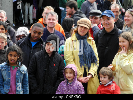 tourists watching street performer in Covent Garden London Uk - Stock Photo