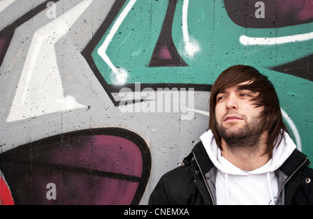 Young man posing in front of a colorful graffiti wall  - Stock Photo