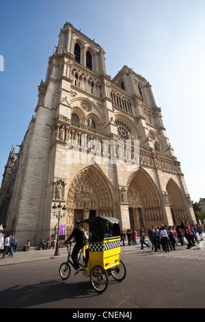 Tourist taxi rickshaw in front of Notre Dame, Paris, France - Stock Photo